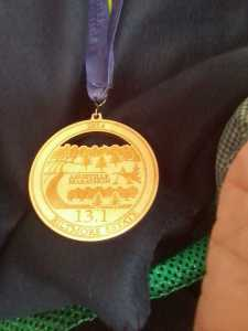 Medal made from local wood against finisher's fleece blanket